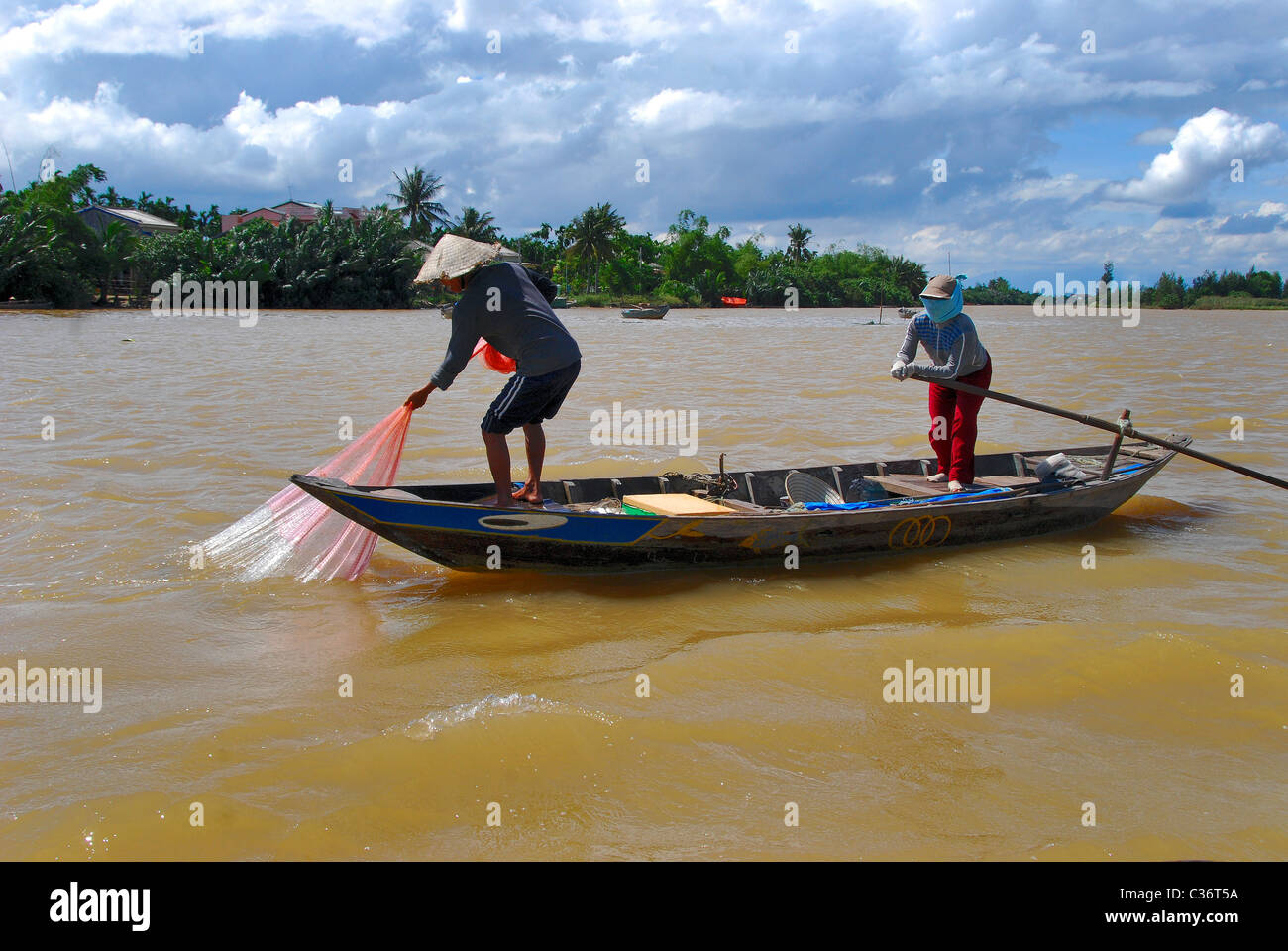 Local fisherman and wife pulling up fishing nets near Cai Be, Mekong Delta, Vietnam - Stock Image
