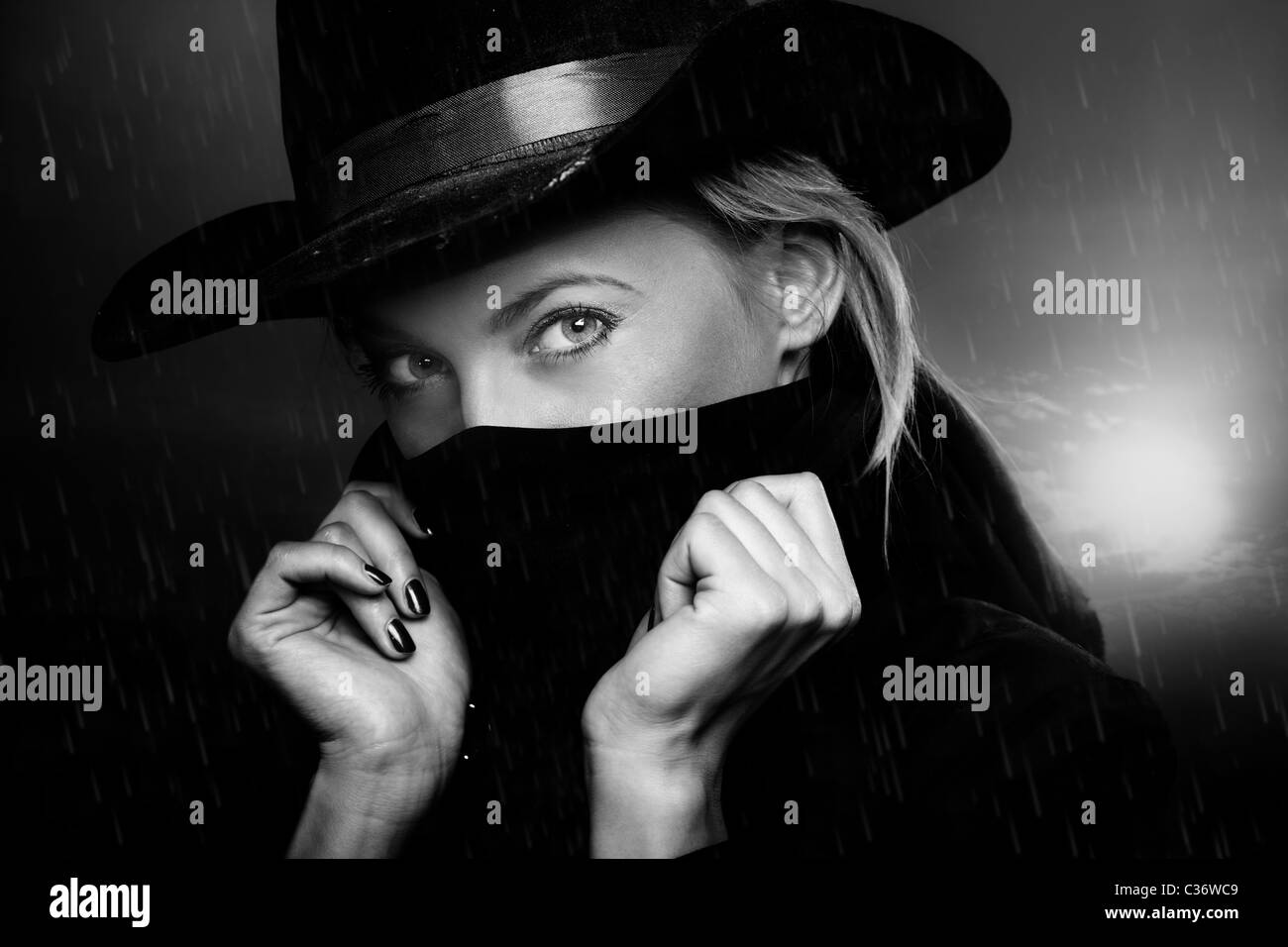 Criminal woman with cowboy hat at twilight under the rain. Natural light and shadows - Stock Image