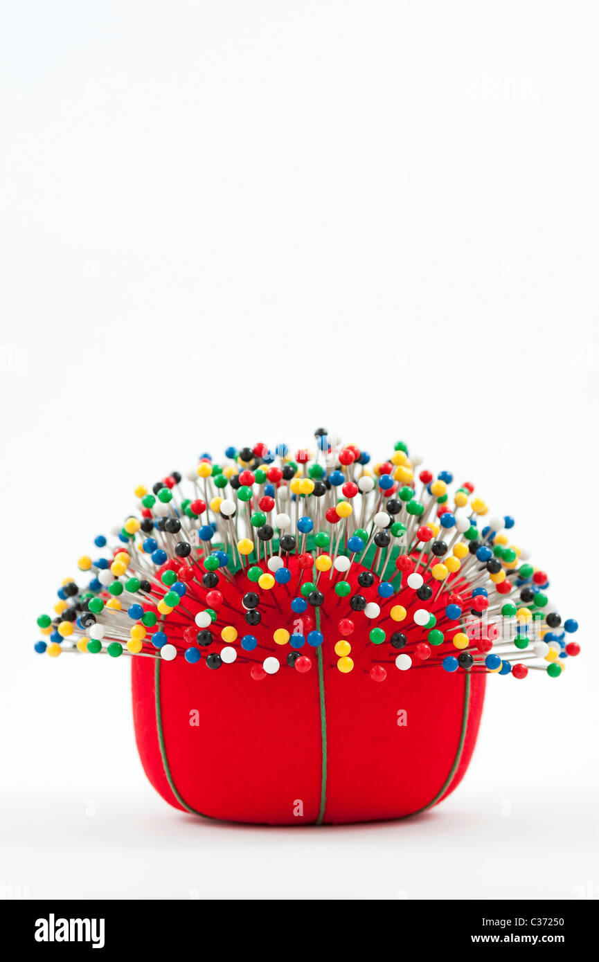 Red pin cushion with multi colored pins stuck in cushion - Stock Image