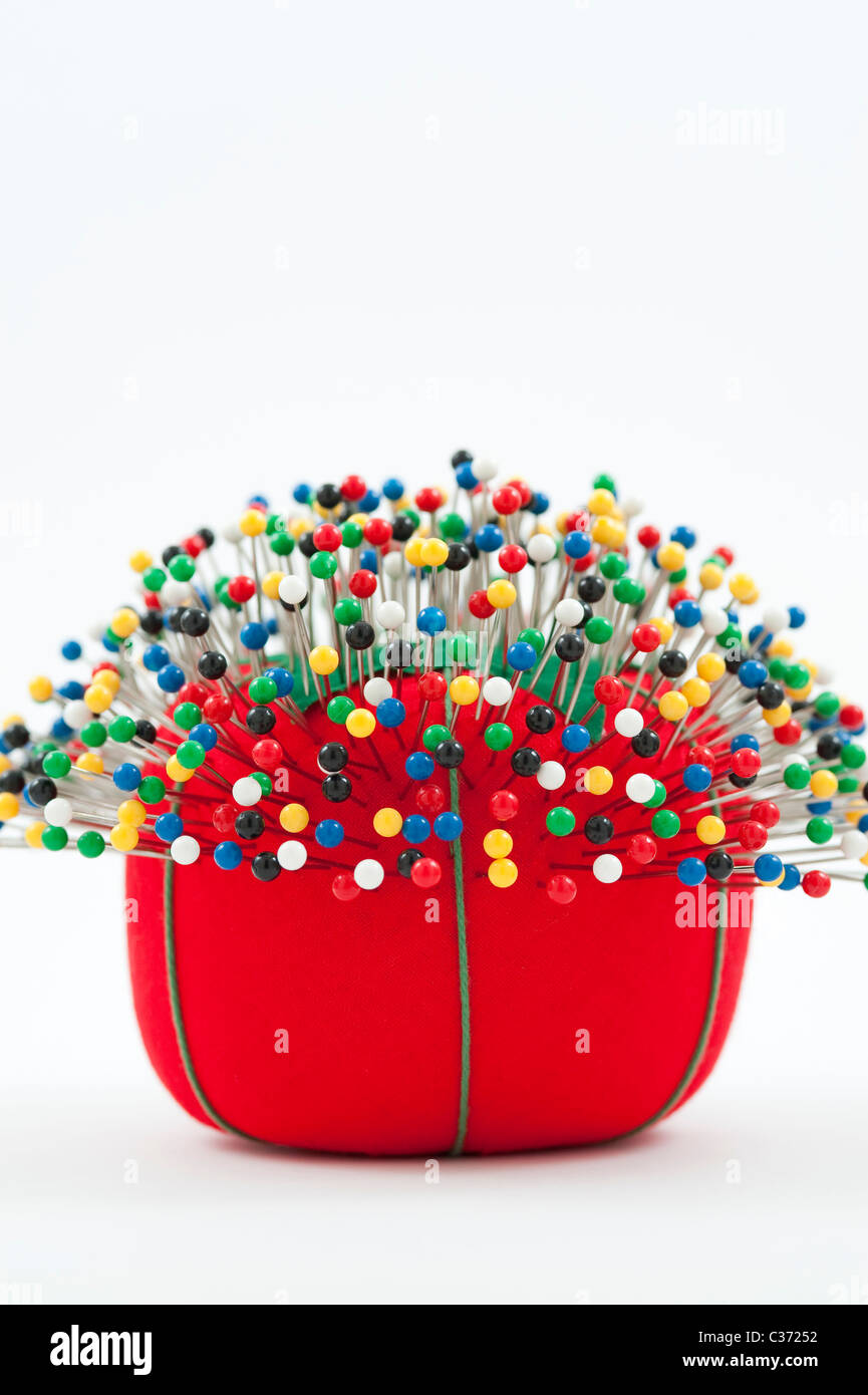 Red pin cushion with multi colored pins stuck in cushion still life studio image - Stock Image