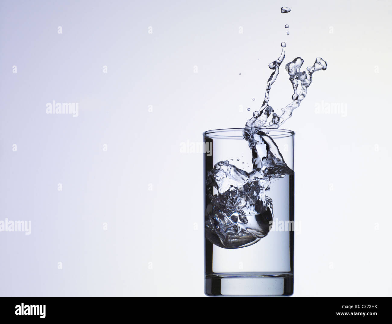 Cube of ice dropping into glass of water - Stock Image