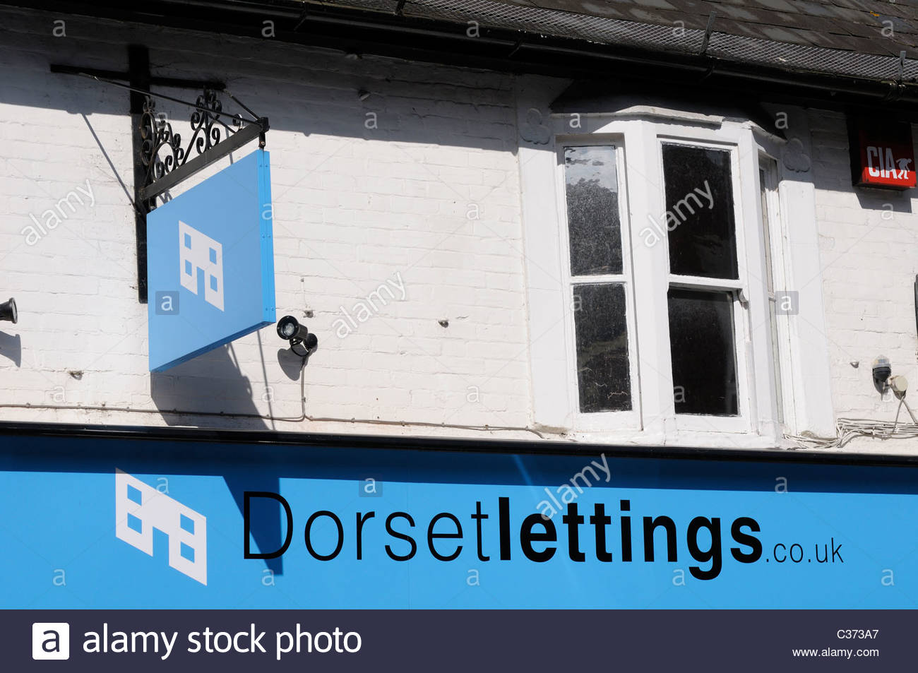 Looking u at the signs above Dorset property lettings agent  office in Wimborne Minster, Dorset England - Stock Image