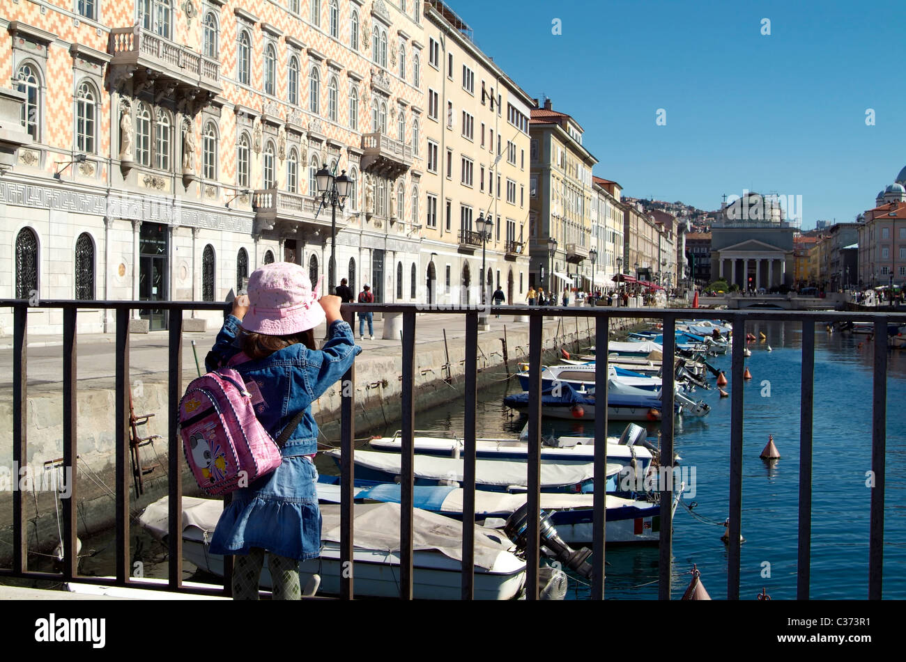A lonesome little girl is looking to some boats in a canal at the Adriatic sea. - Stock Image