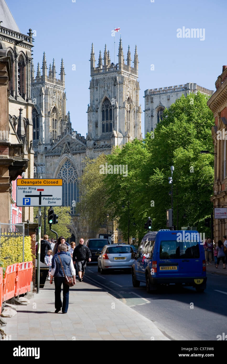Pedestrians walking the streets of York City Centre with a view of the towers of York Minster York North Yorkshire - Stock Image