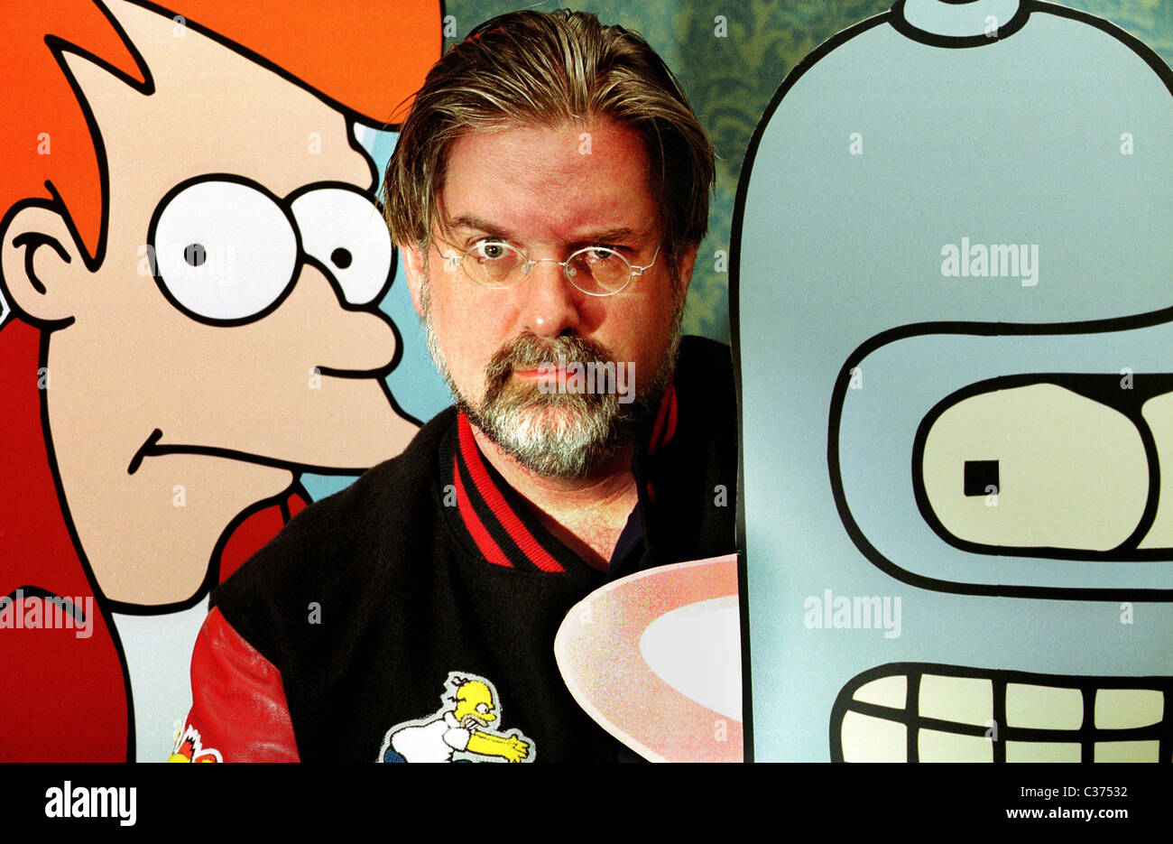 Matt Groening with cardboard cut-outs of Fry and Bender, characters from his animated show, Futurama. - Stock Image