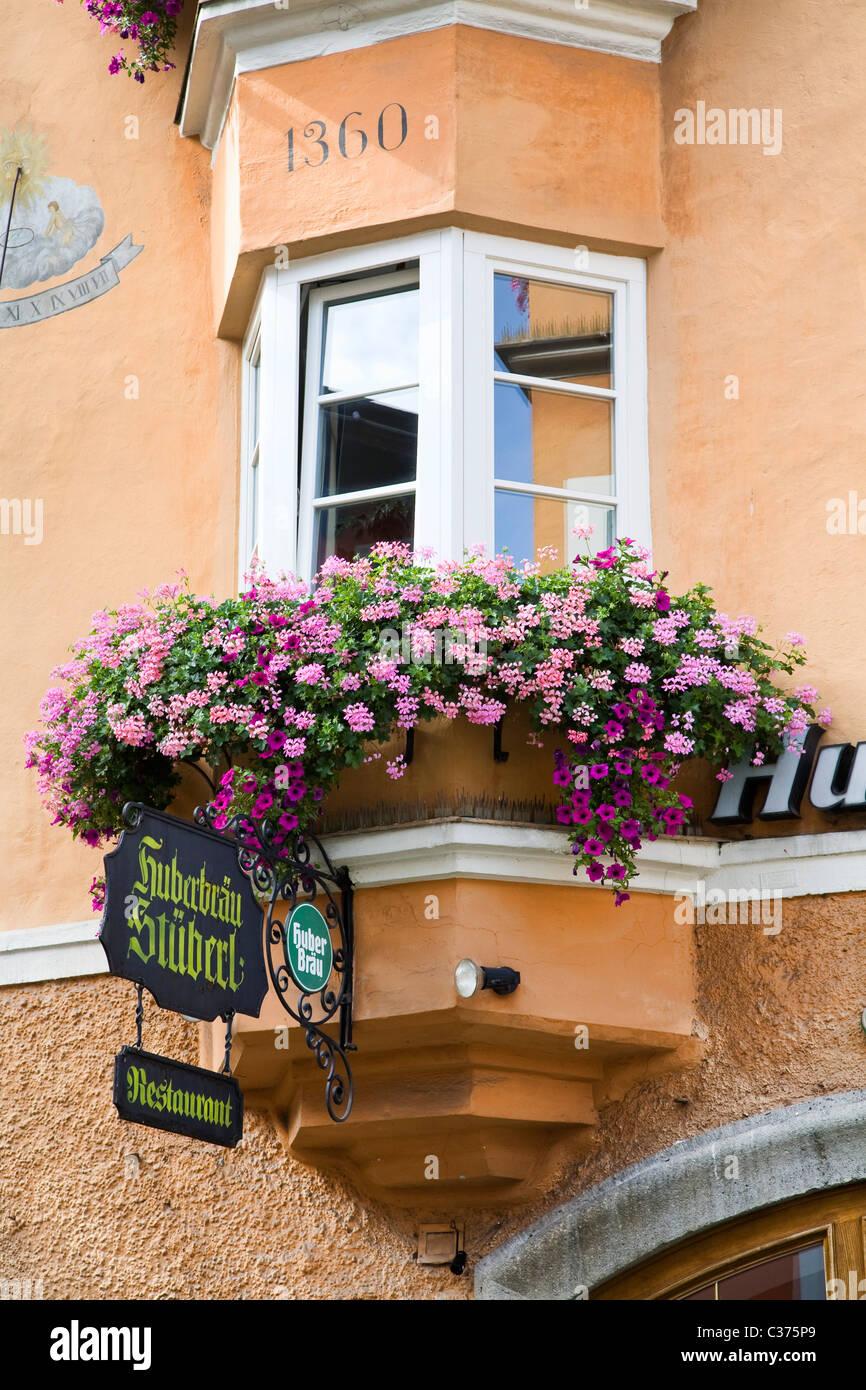 A flower box decorates a bay window in Kitzbuhel Austria - Stock Image