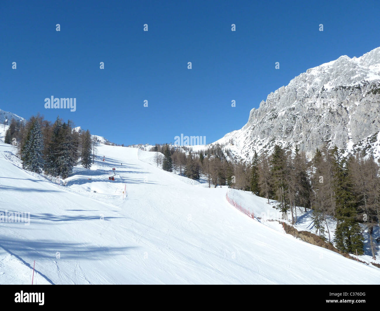 A fresh primed ski slope with a cloudless blue sky. - Stock Image