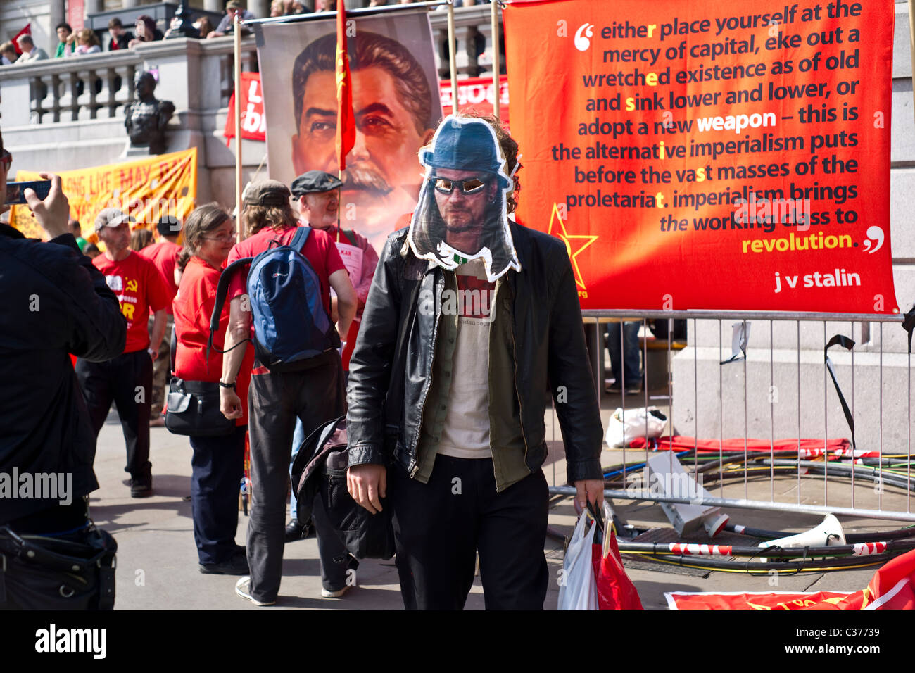 Man in Mark Kennedy mask at Mayday gathering in Trafalgar Square - Stock Image