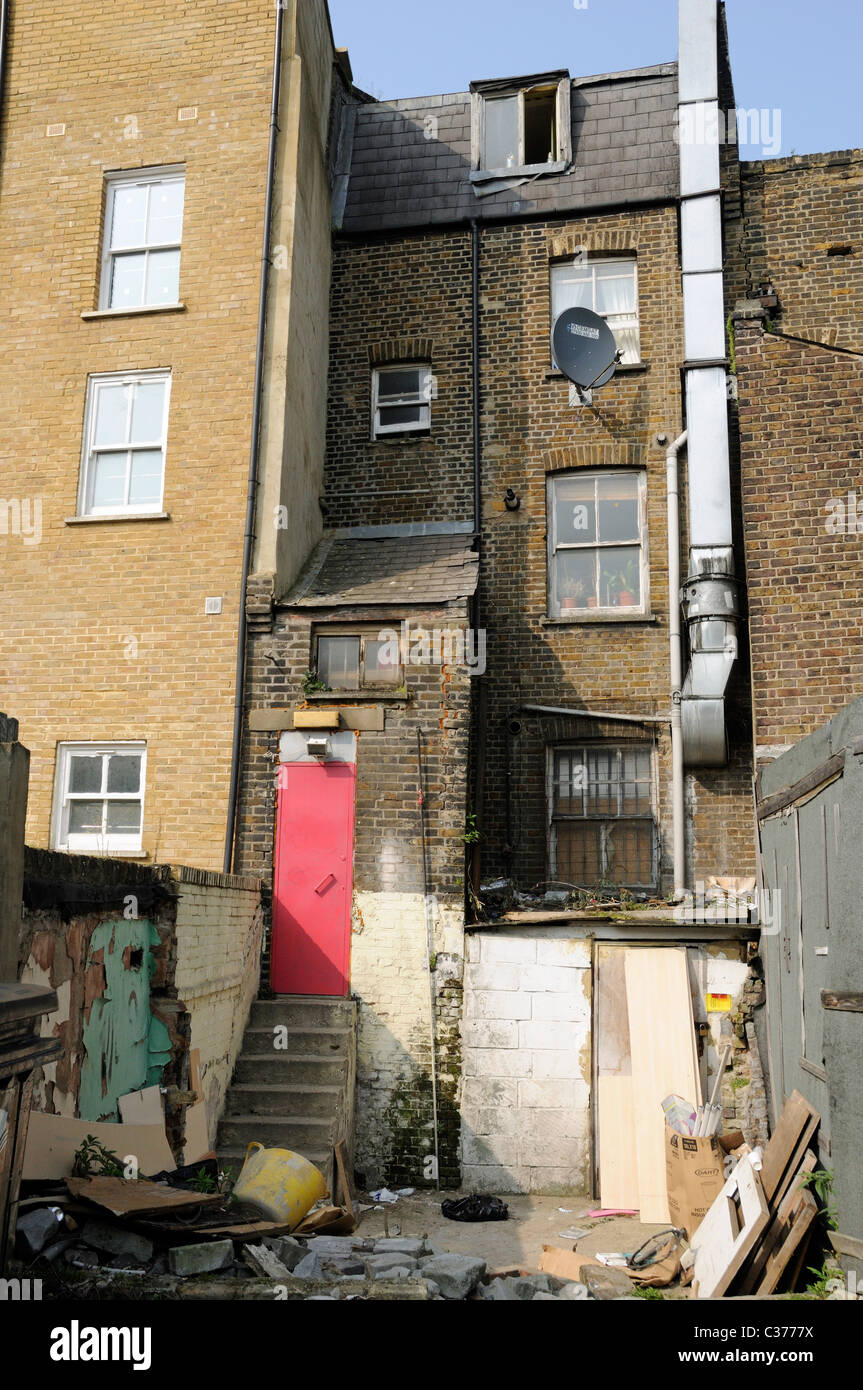 Back of run down house with garden open to the street, Hackney London UK - Stock Image