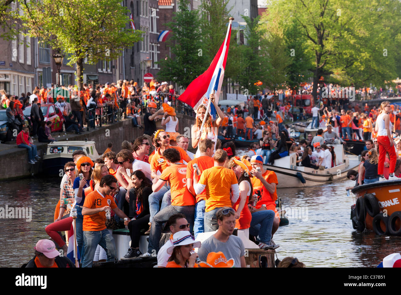Kingsday, the King's birthday (Queensday Queen's day) in Amsterdam Girl on boat waving Dutch flag in traditional - Stock Image