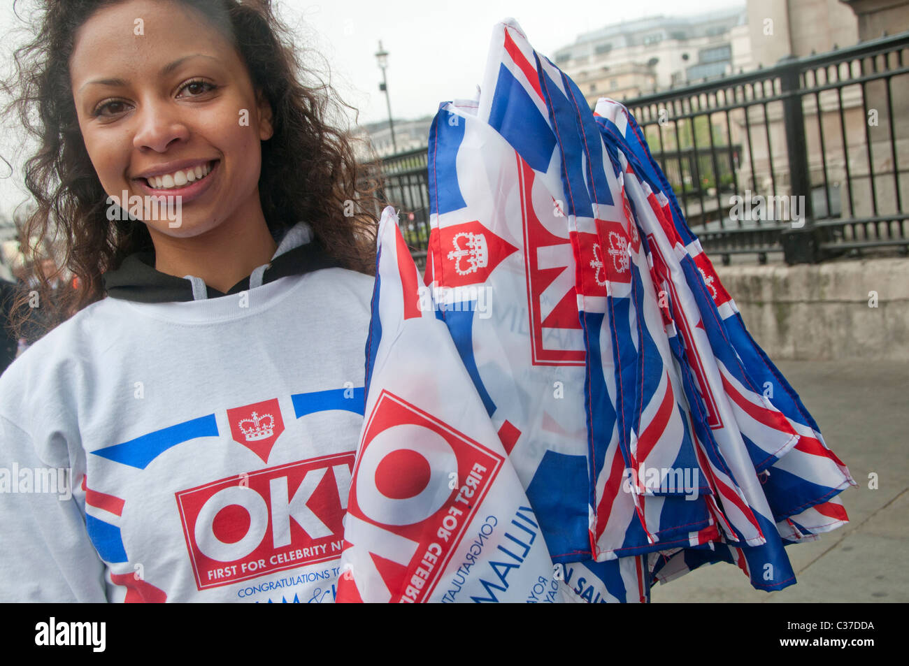 April 29th 2011 Royal Wedding. Trafalgar Square. Woman handing out Union Jacks, given away by OK magazine. - Stock Image