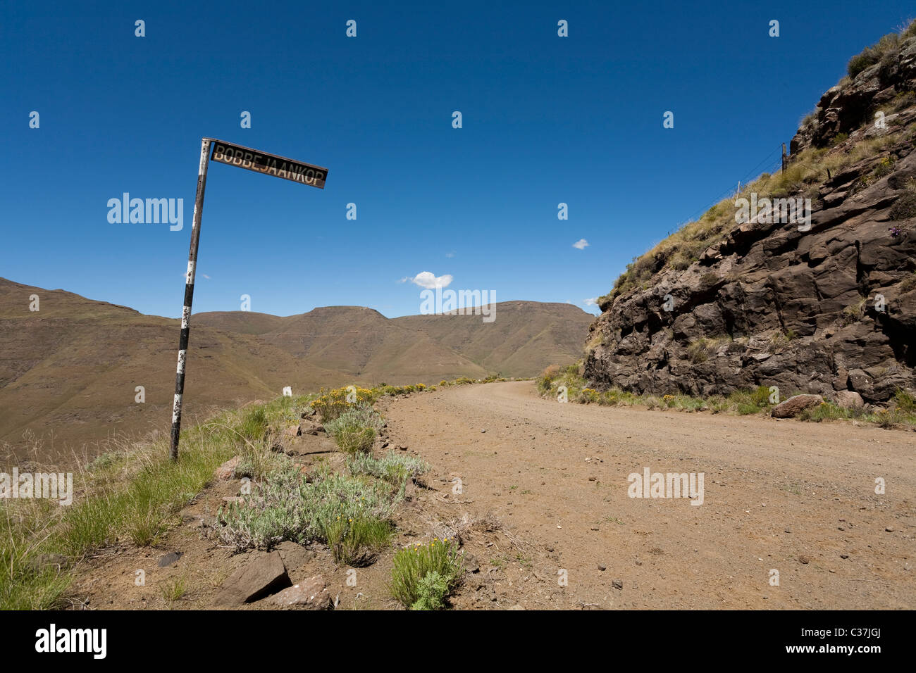 A road sign on a bend in the dirt road near Rhodes, South Africa. - Stock Image