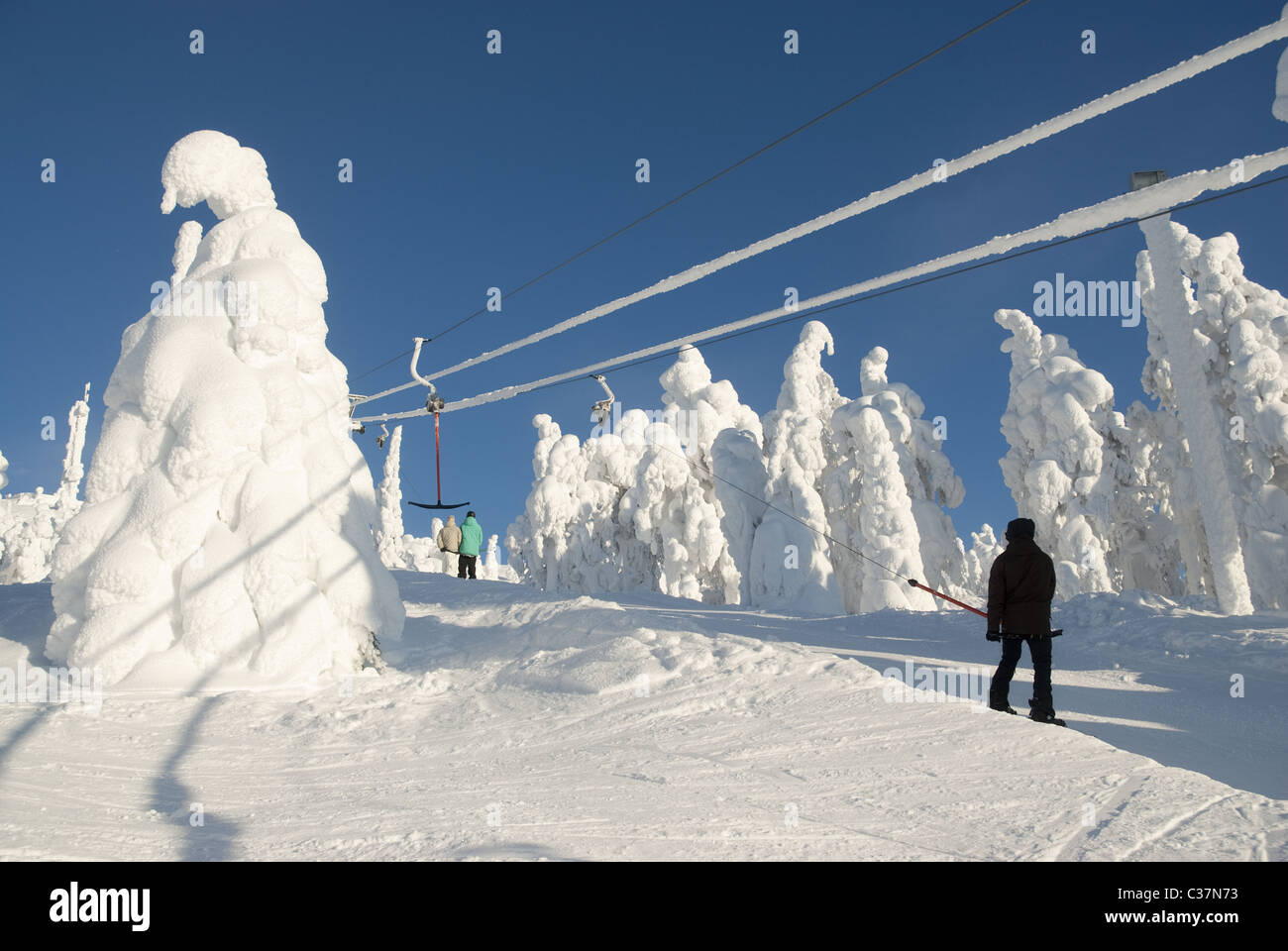 Skiers in a t-bar ski-lift in Ruka, Finland. - Stock Image