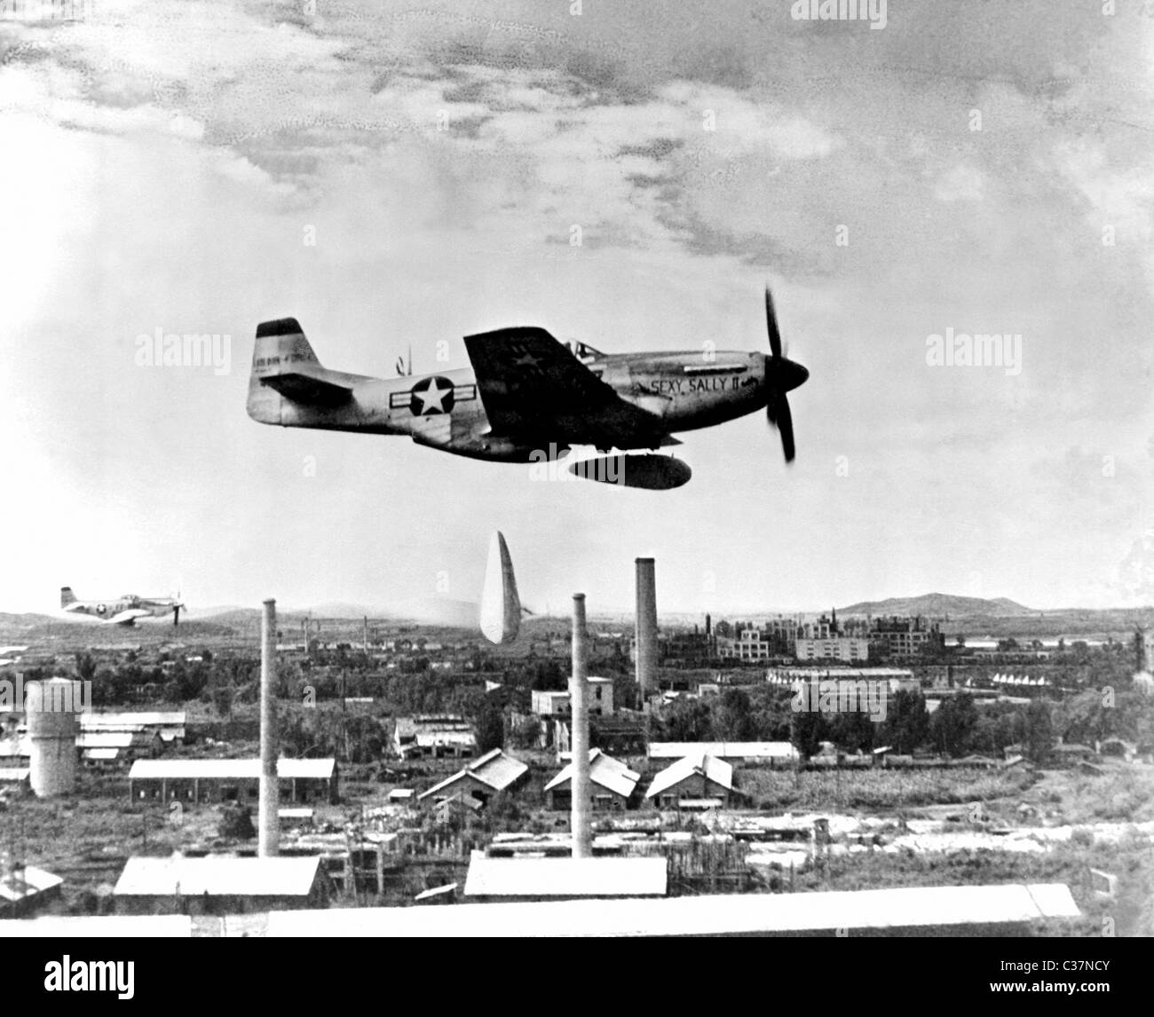 F-51 Mustang of the U.S. Fifth Air Force's 18th bomber wing releases two Napalm bombs over military target in - Stock Image
