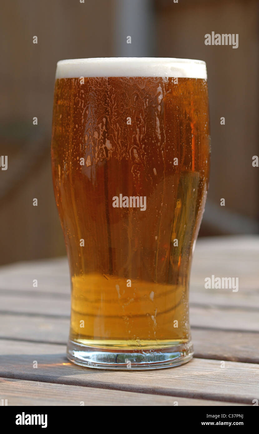 Pint of refreshing ale on table in pub beer garden table - Stock Image