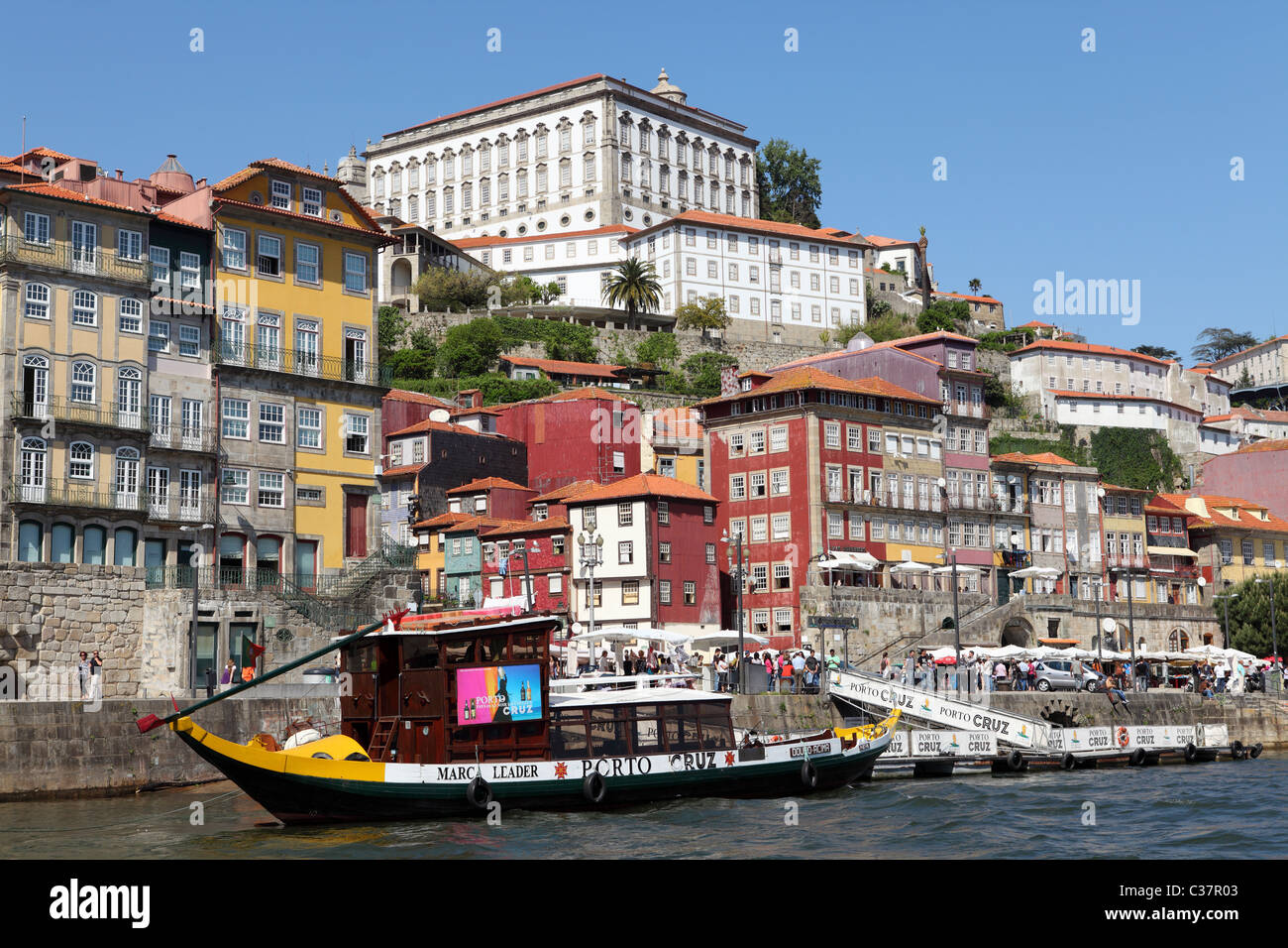 A cruise boat docks by the riverside Ribeira district of Porto, Portugal. - Stock Image