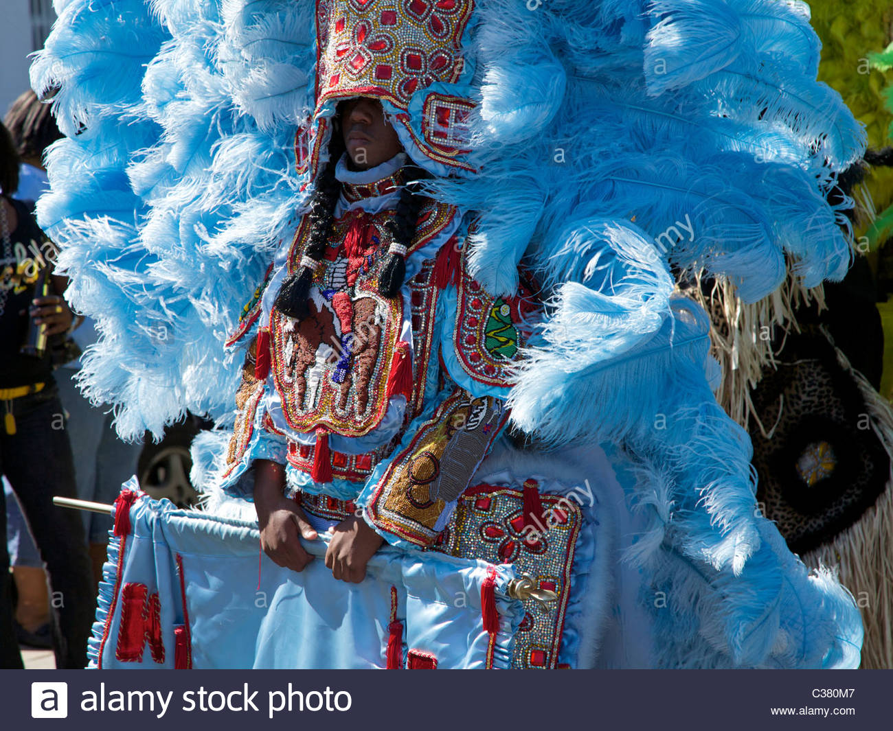 A Mardi Gras Indian wearing traditional hand-made costume sewn from feathers and beads. New Orleans, Louisiana. - Stock Image