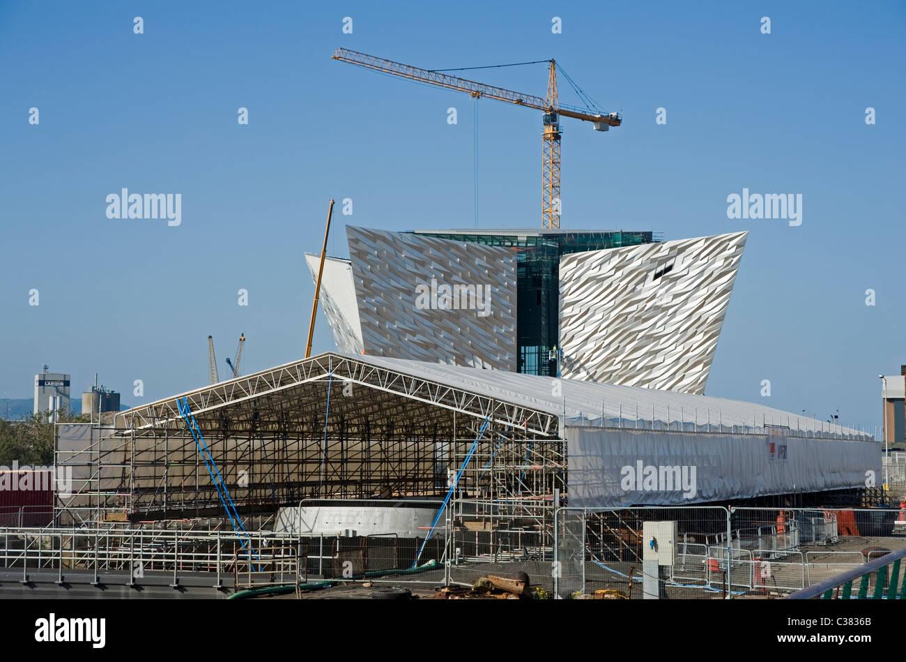SS Nomadic undergoing restoration in the Titanic Quarter, Belfast. Titanic Museum under constuction in background. - Stock Image