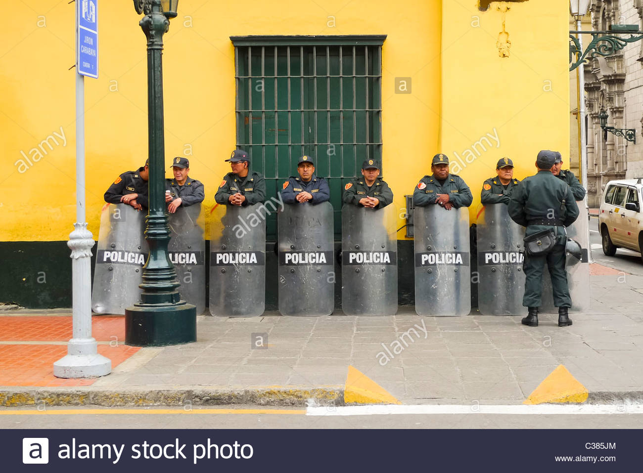 Group of Police lined up against a wall holding shields. Lima, Peru - Stock Image