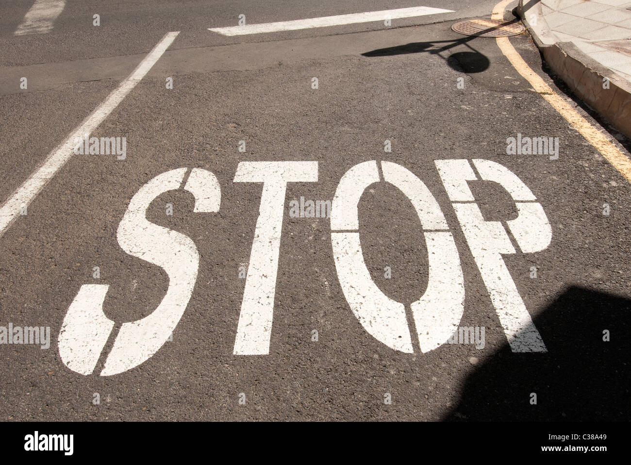 Road junction with Stop written on the tarmac Fuerteventura Canary Islands - Stock Image