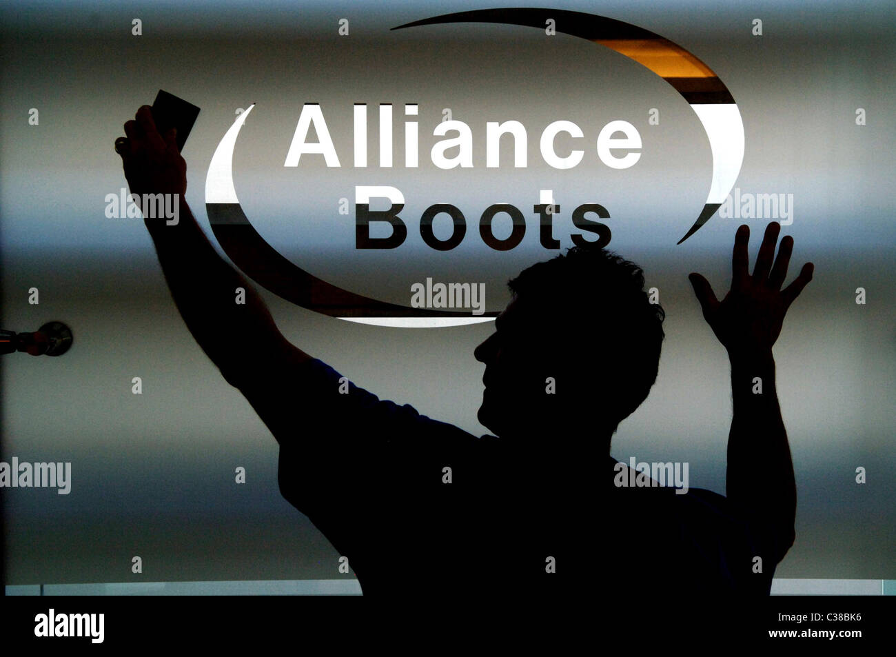 A worker cleaning an Alliance Boots frosted window logo. - Stock Image