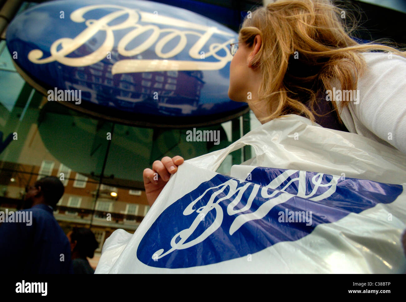 A woman with a Boots shopping bag on Oxford Street, London - Stock Image