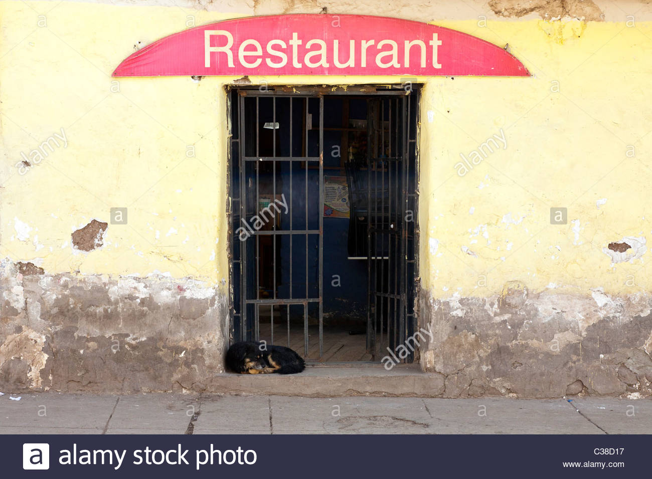 Dog Sleeping in front of a small Peruvian restaurant. Cusco, Peru. - Stock Image