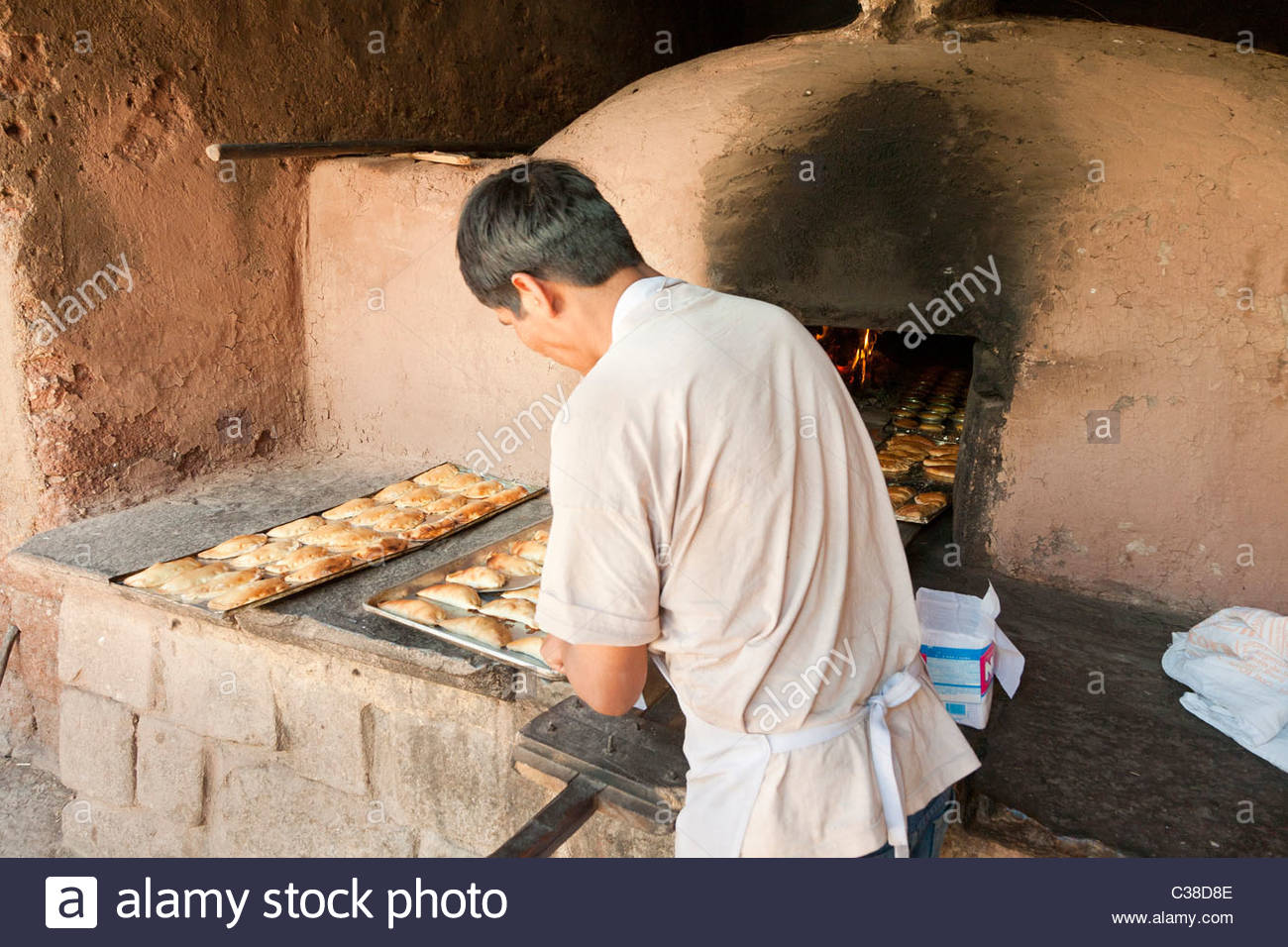 Peruvian baker removes Empanadas (small meat pies) from a wood-fired adobe oven. Pisac, Peru. - Stock Image