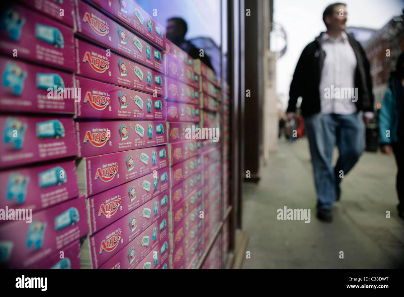 A pile of Argos catalogues stack insde a store window. Part of the Home Retail Group. - Stock Image
