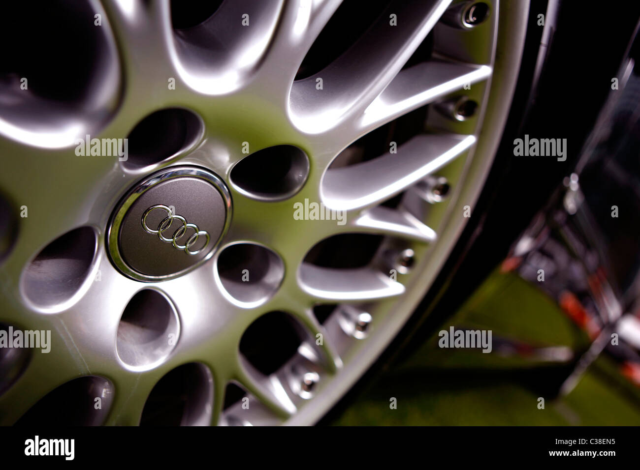 A wide-angle picture of the alloy wheels of a highly polished black Audi on the Motorexpo exhibition in Canary Wharf, - Stock Image