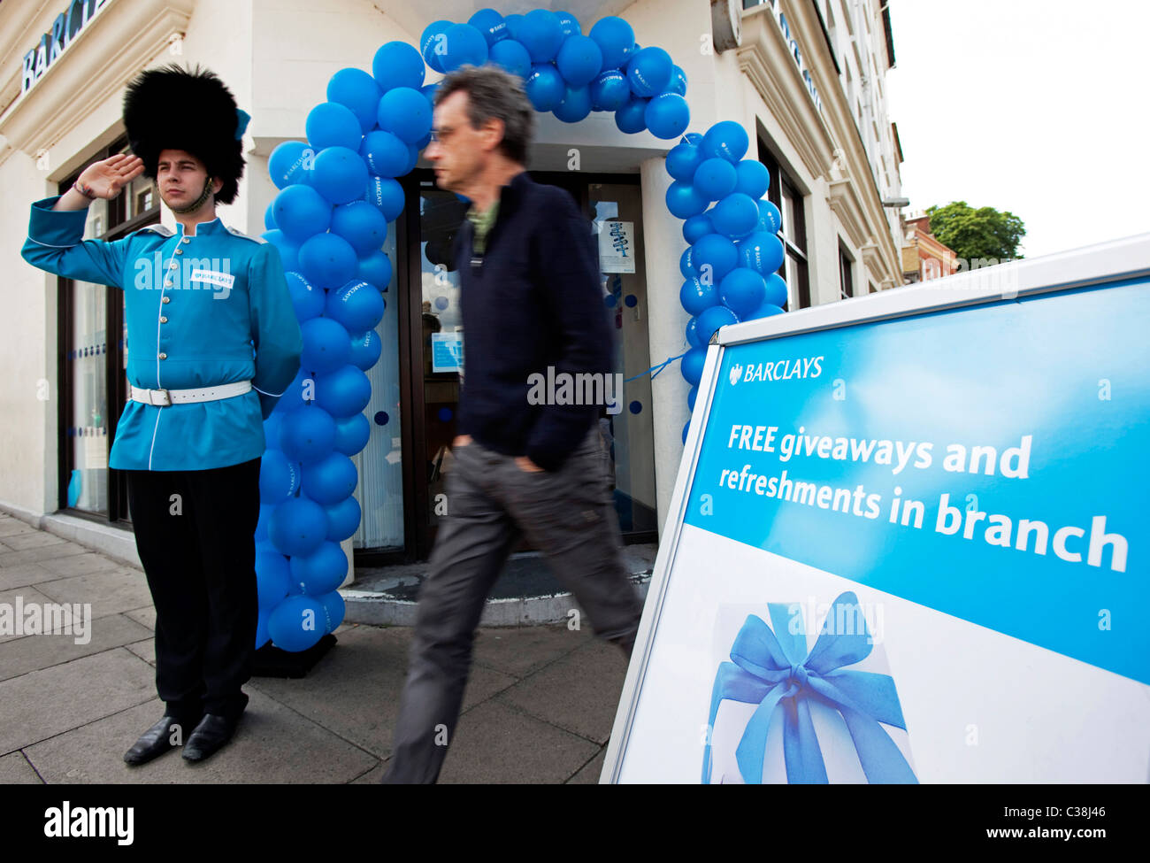 A person passes by a branch of Barclays bank, Cambridge. The guard is part of a PR campaign being run by Barclays. - Stock Image
