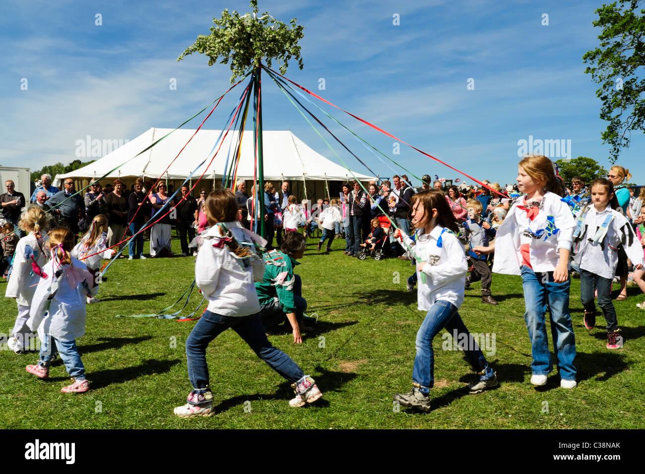 Dilwyn village show, Herefordshire, UK. Girls maypole dancing in England. Schoolgirls dance around the maypole at Stock Photo