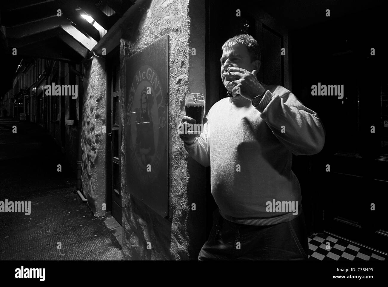 A man enjoys a pint of Guinness outside Sissy McGinty's Pub, Castlerea, County Roscommon, Ireland. - Stock Image