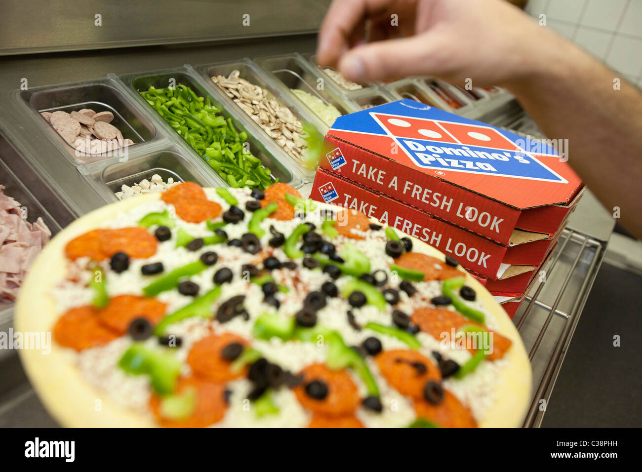 A Domino's Pizza employee preparing a fresh pizza ready for the cooking oven. - Stock Image