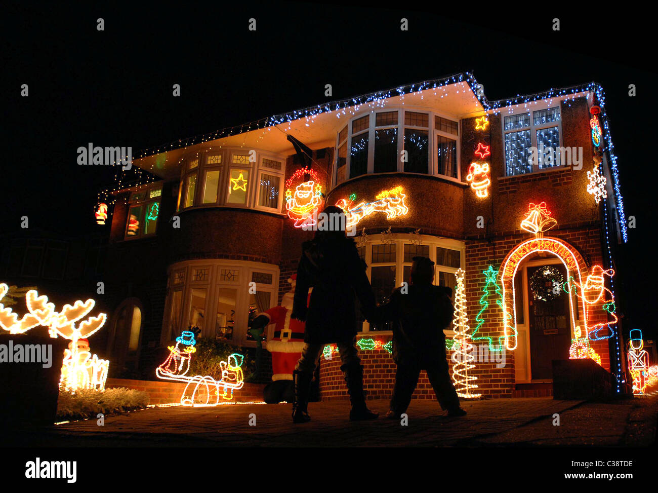 young children stand outside a decorated house at christmas time stock image