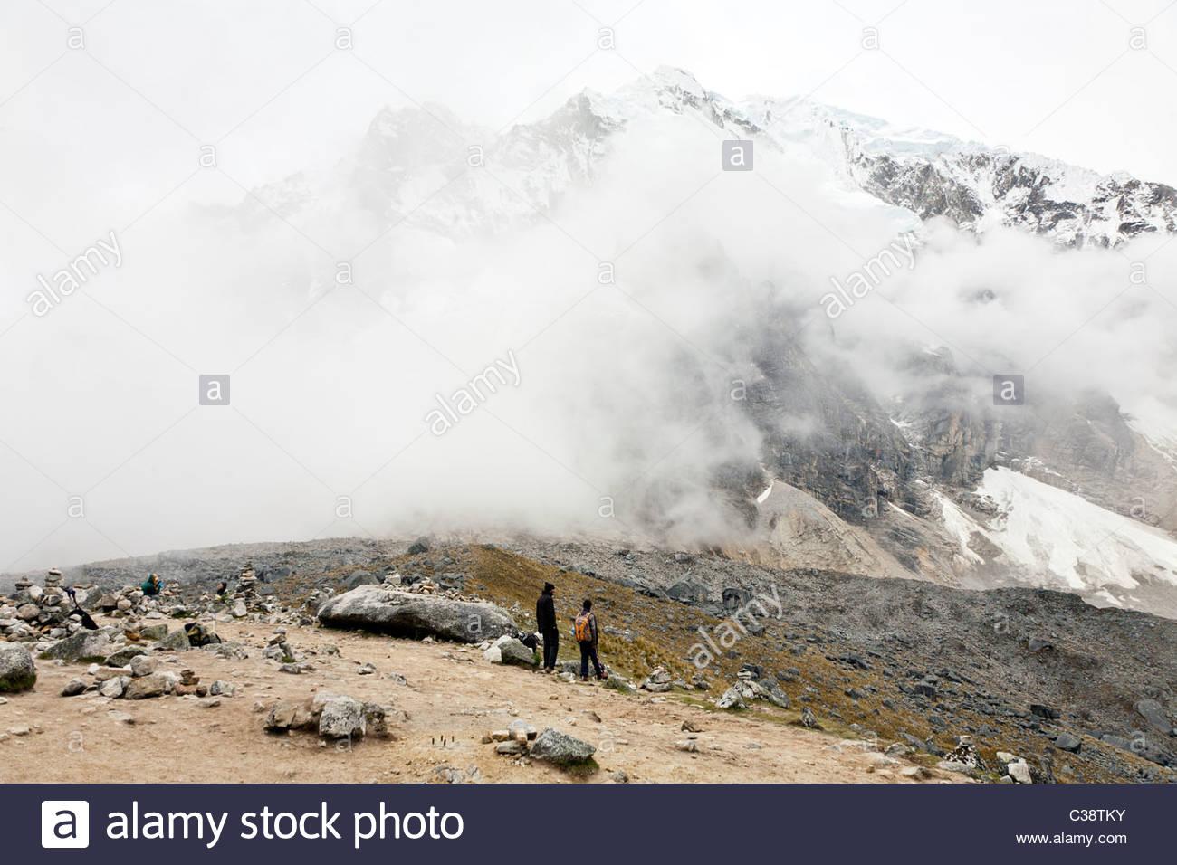 A hikers marvels at the immense size of Salkantay mountain at Salkantay Pass (4800m). Near Mollepata, Peru. Stock Photo