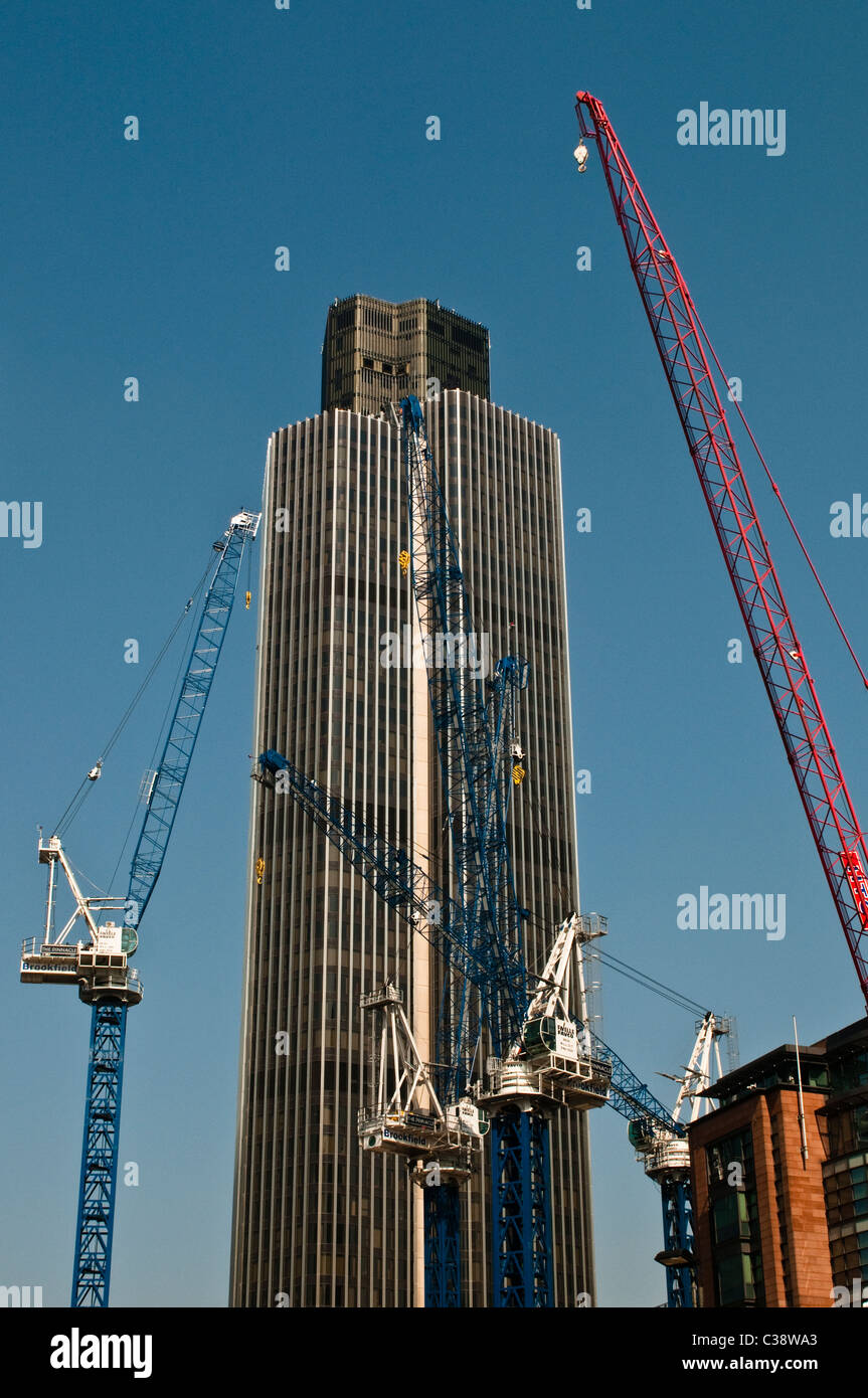 Tower 42, NatWest tower and cranes, City of London, UK - Stock Image