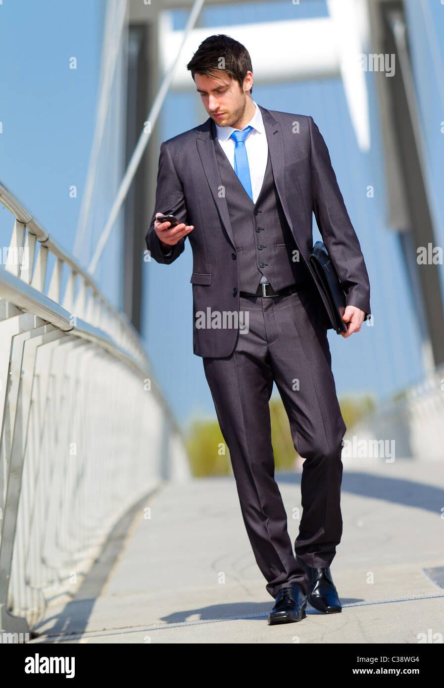 Man walking looking at phone Stock Photo