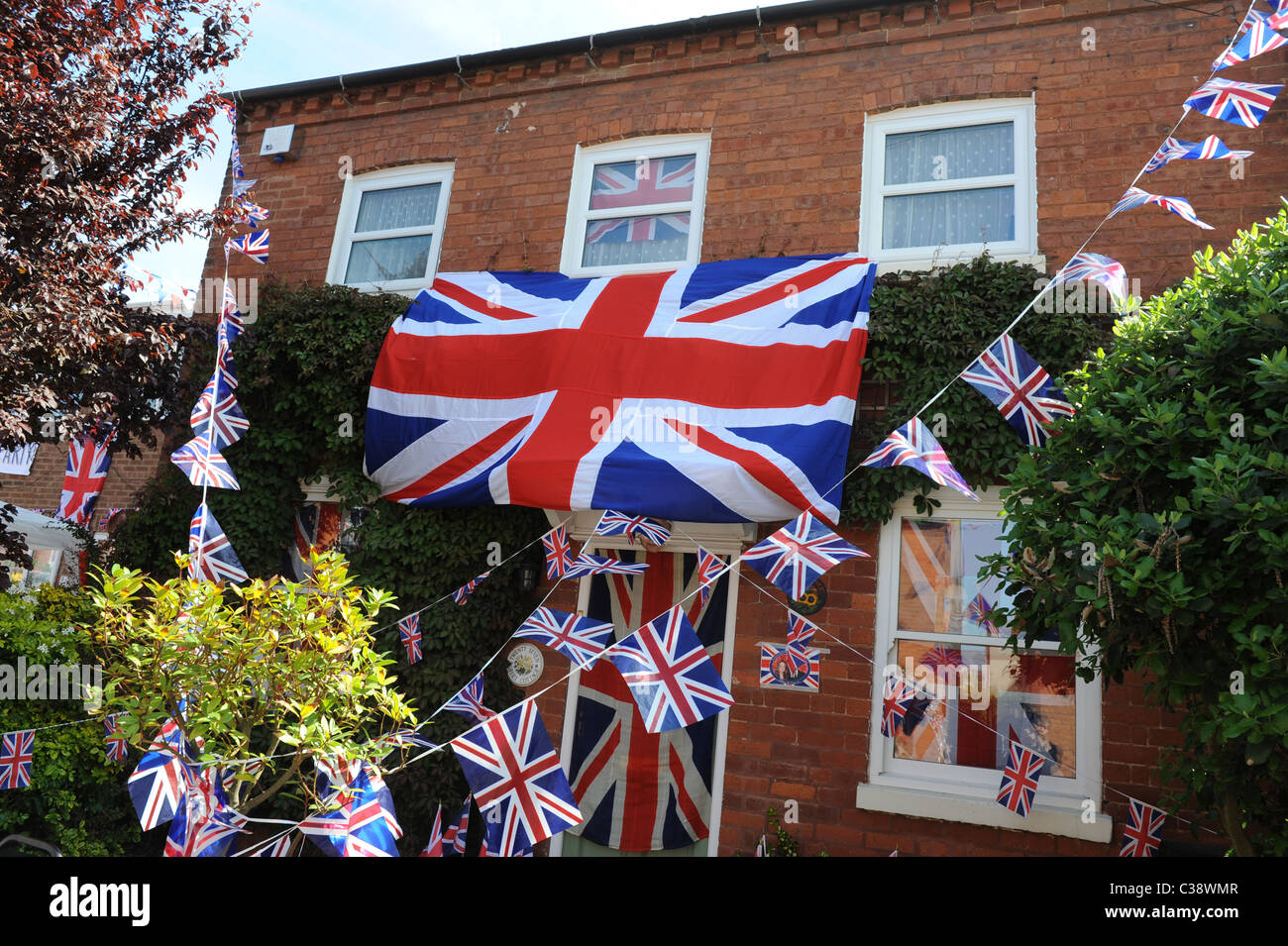 House decorated in Unions Jack flags to celebrate royal wedding in Worcester for a street party Uk - Stock Image