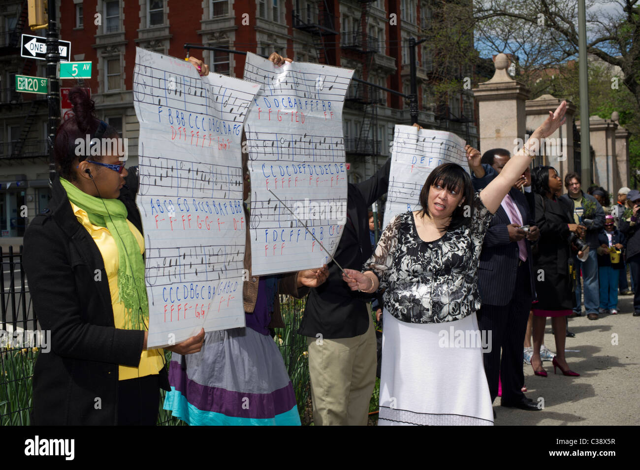 A woman conducts a bell ringers performance in Mt. Morris Park in the Harlem Heritage Rose District in New York - Stock Image