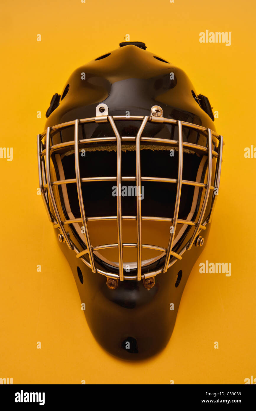 A Black Hockey Goalie Helmet On A Gold Background Some Scratches