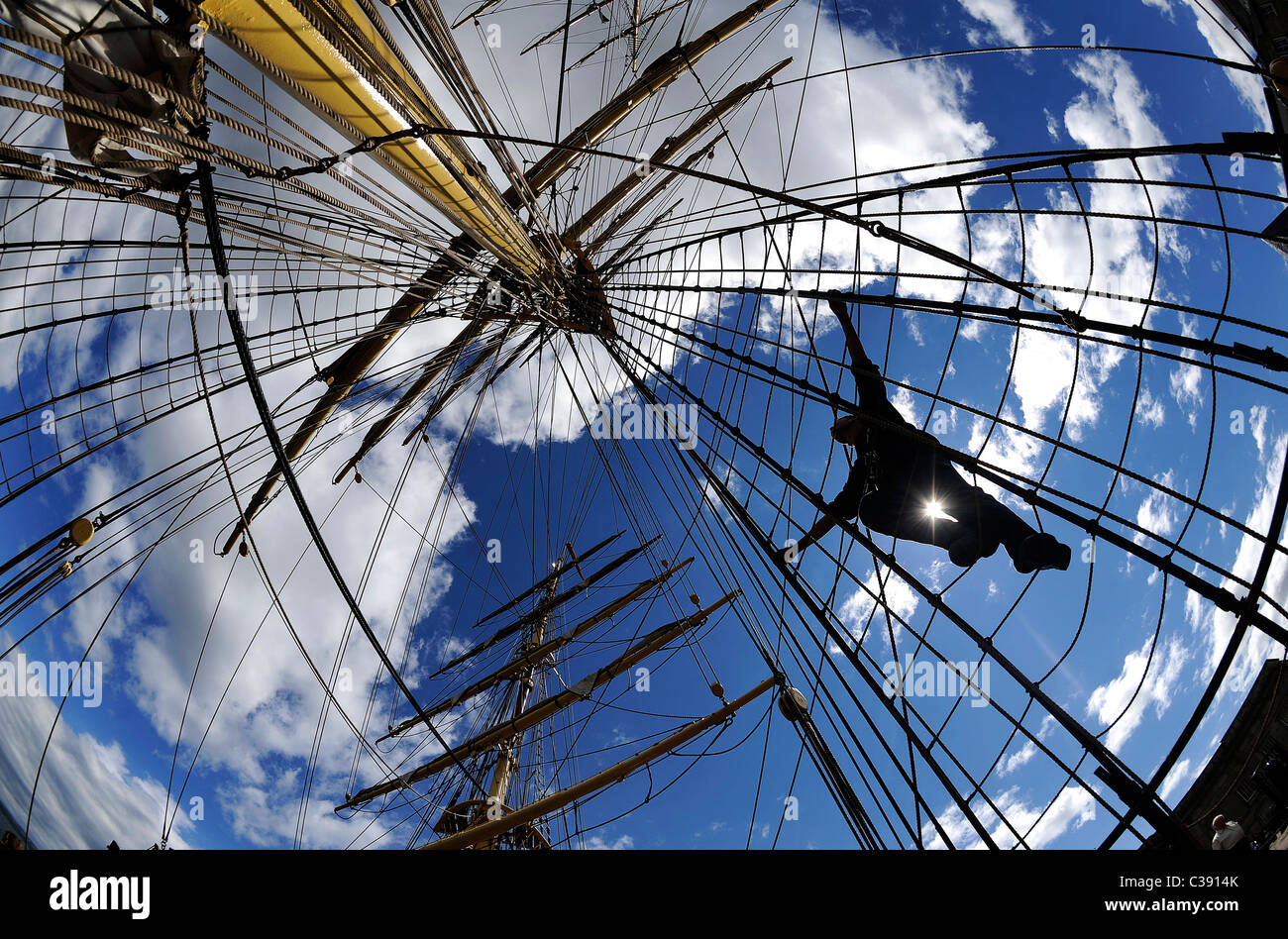 A crew member climbs the rigging on the Danish tall ship Georg Stage as it sails up the River Clyde in Scotland. - Stock Image