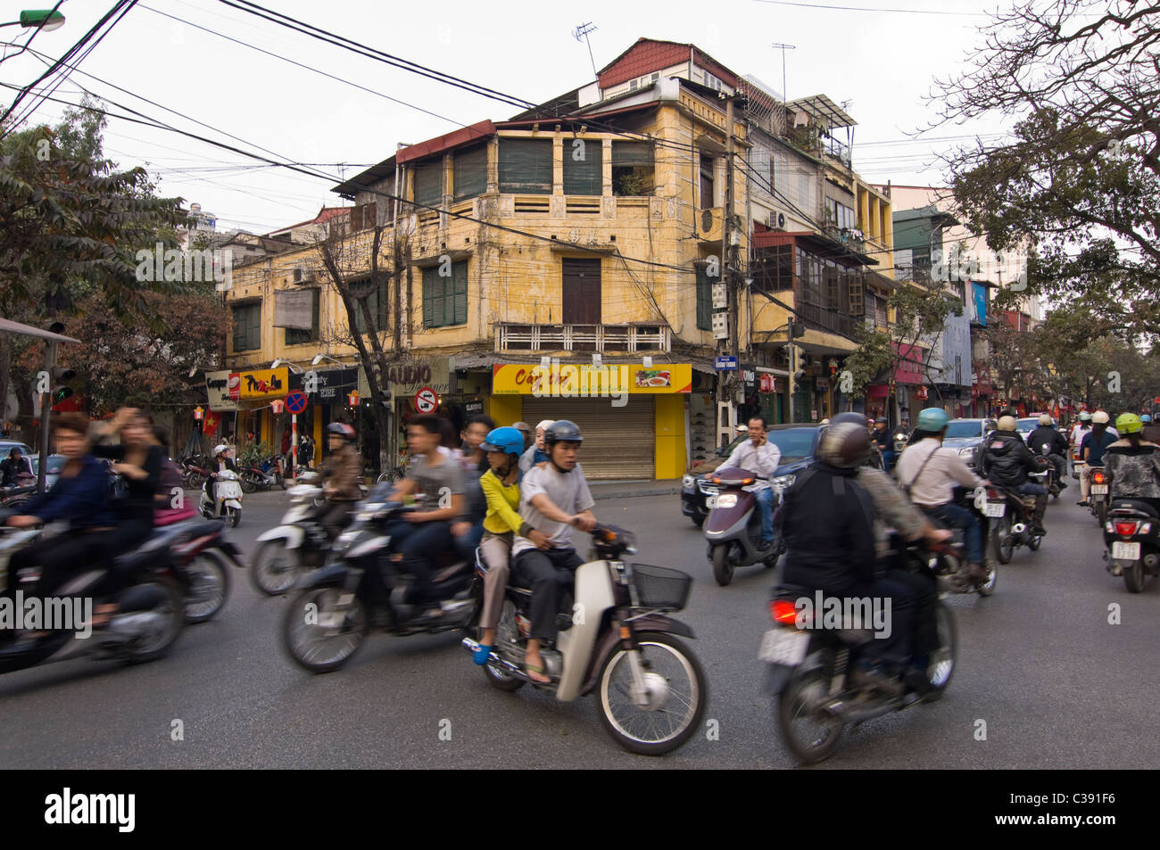 Horizontal wide angle of disorganised chaos on Hanoi's streets with mopeds, motorbikes & scooters everywhere - Stock Image
