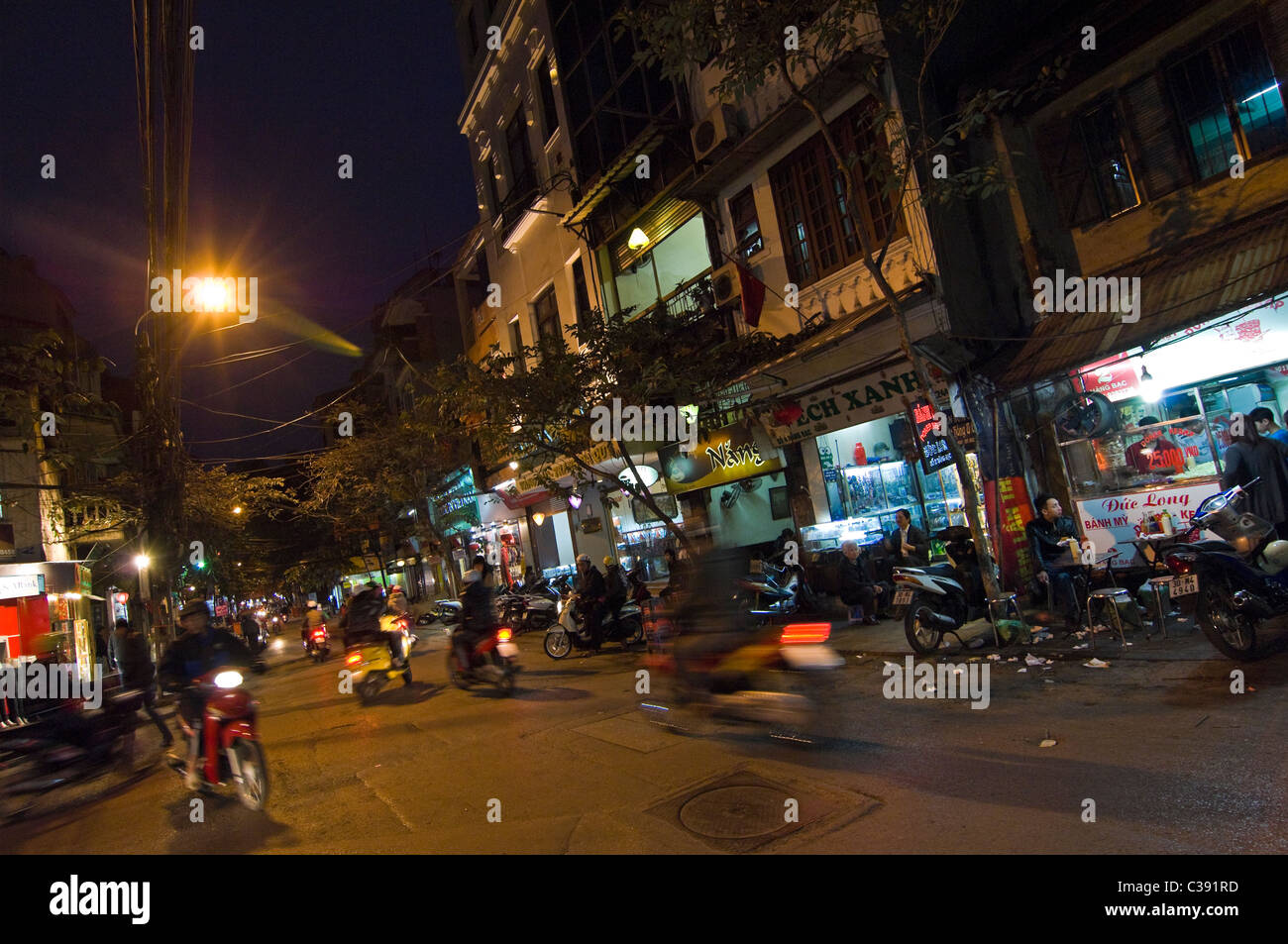 Horizontal night view of a typical streetscene of the Old Quarter in Hanoi, with shops open for business and mopeds - Stock Image