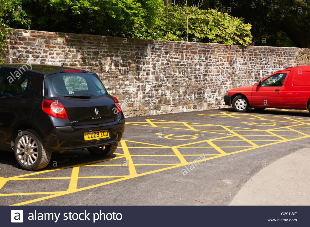 a motor car and a red van parked in a disabled parking bay - Stock Image