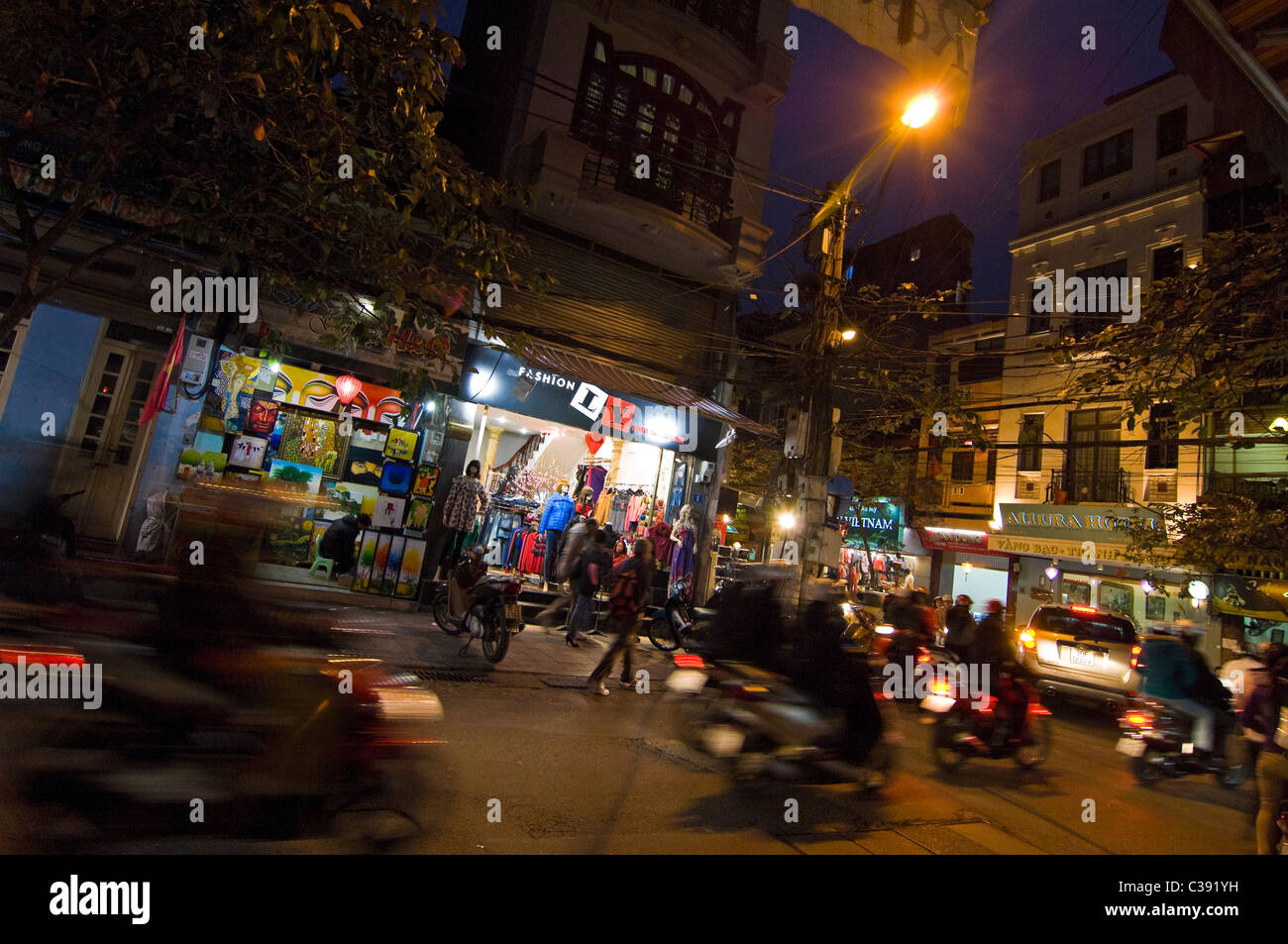 Horizontal wide angle of shops and mopeds, a typical streetscene of the Old Quarter lit up at night, in central - Stock Image