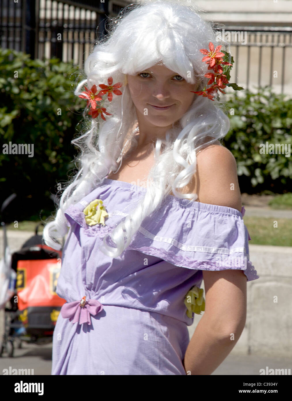 A smiling young girl in a purple dress dances for the public in Trafalgar Square on a sunny May afternoon. - Stock Image