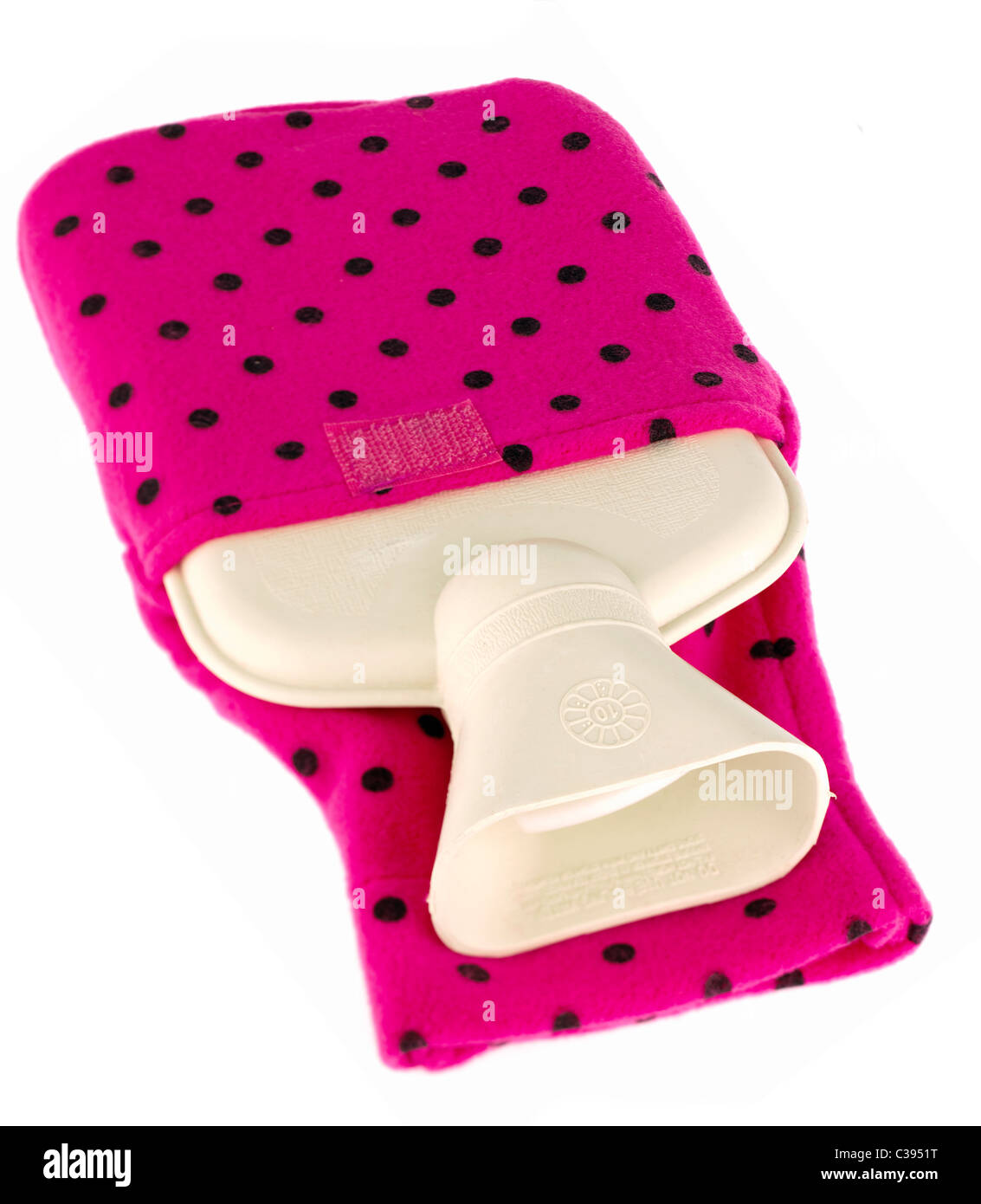 Small rubber hot waterbottle encased in a pink with black spots soft nylon cover - Stock Image