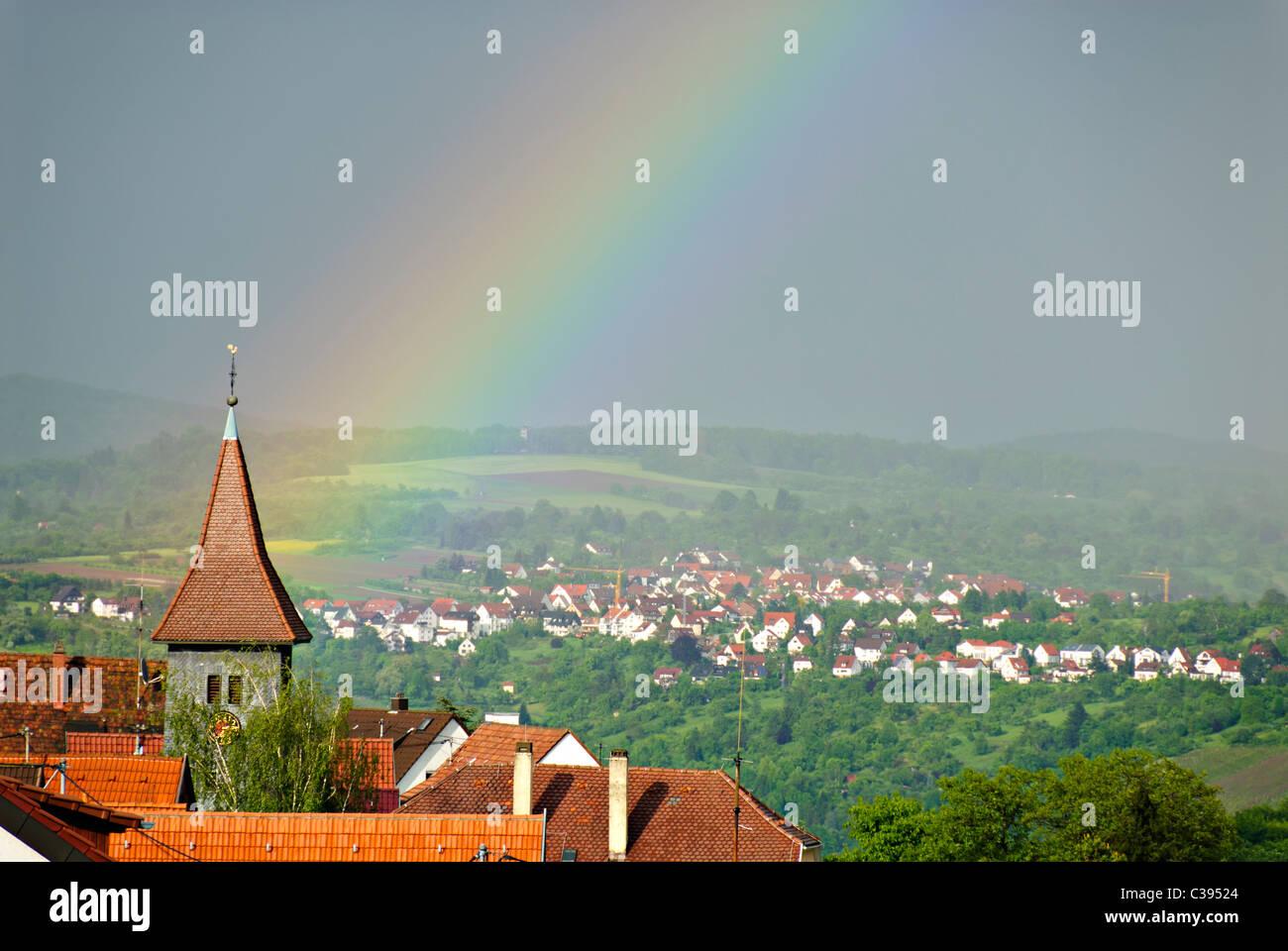 Rainbow over church, Germany, Europe - Stock Image