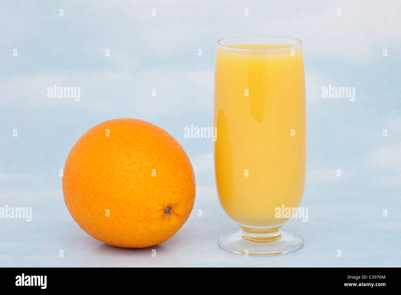 One glass of fresh orange juice with a whole orange containing vitamin C against a blue sky background - Stock Image